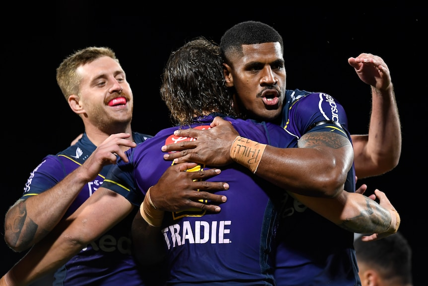 Three Melbourne Storm NRL players embrace after a try was scored against Wests Tigers.