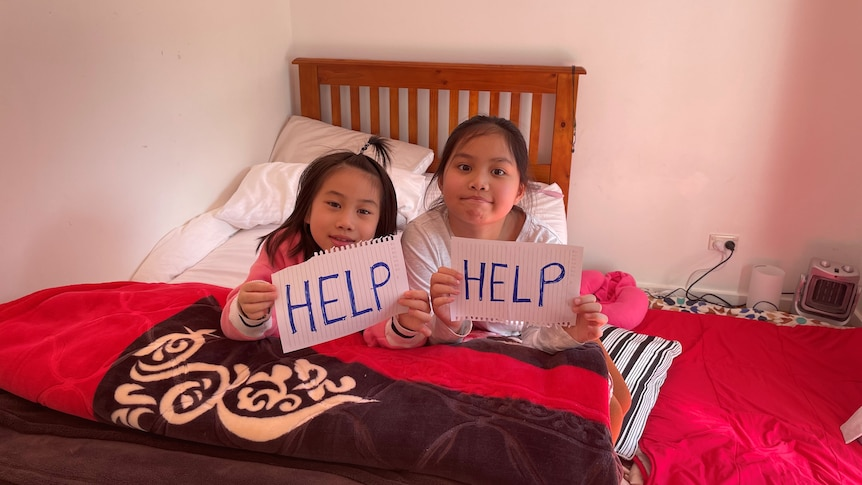 """Two young girls on a bed with hand-written signs saying """"HELP""""."""