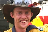 Man in bushman's hat and firefighter uniform grins and gives thumbs up as he leans on fire truck.