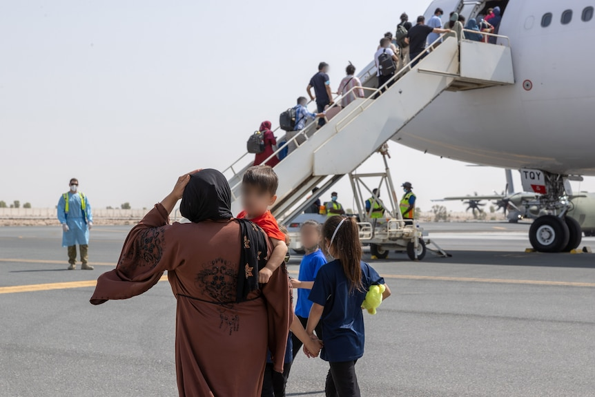 A family walks towards the staircase leading into a plane on a tarmac.