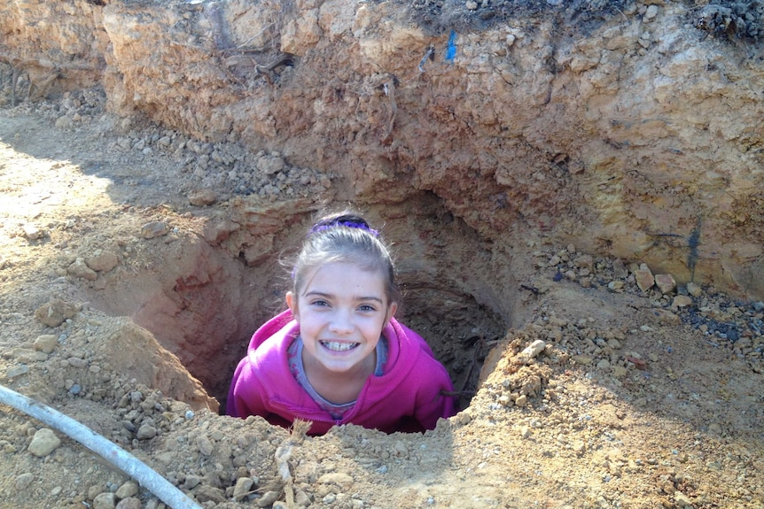 A young girl standing in a hole poking her head out