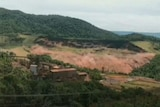 A wall of brown water flooding a green field after a dam collapsed in Brazil.