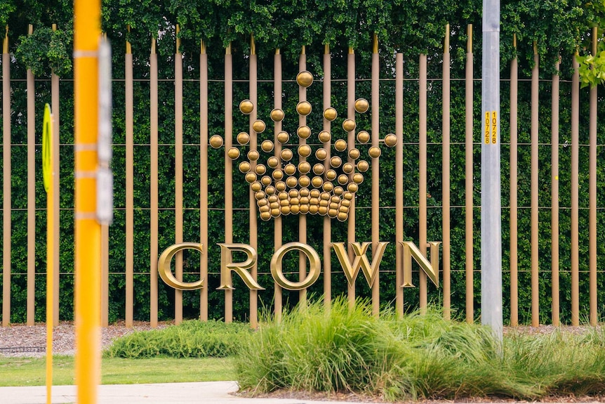 A sign showing the Crown Resorts logo in front of shrubs beside a road.