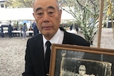 Japanese man wearing suit holds old framed photo of father in uniform