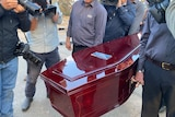 Cemetery authority staff carry a coffin for the Somerton Man's remains.