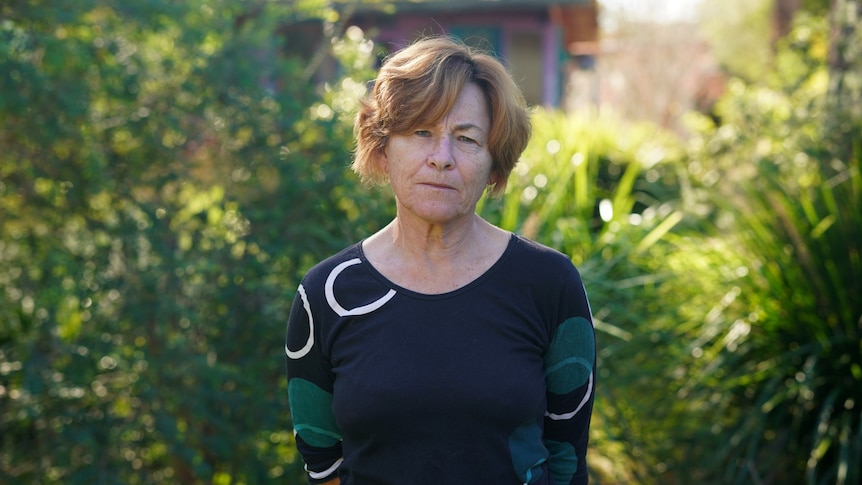A woman stands and looks at the camera in front of a bush