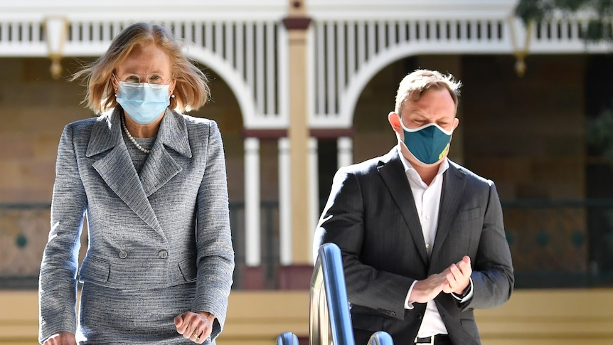 Woman in grey suit and man in dark suit, both wearing masks