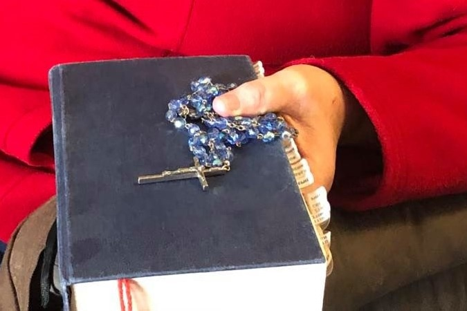 A hand clutches a bible and a bright blue rosary.