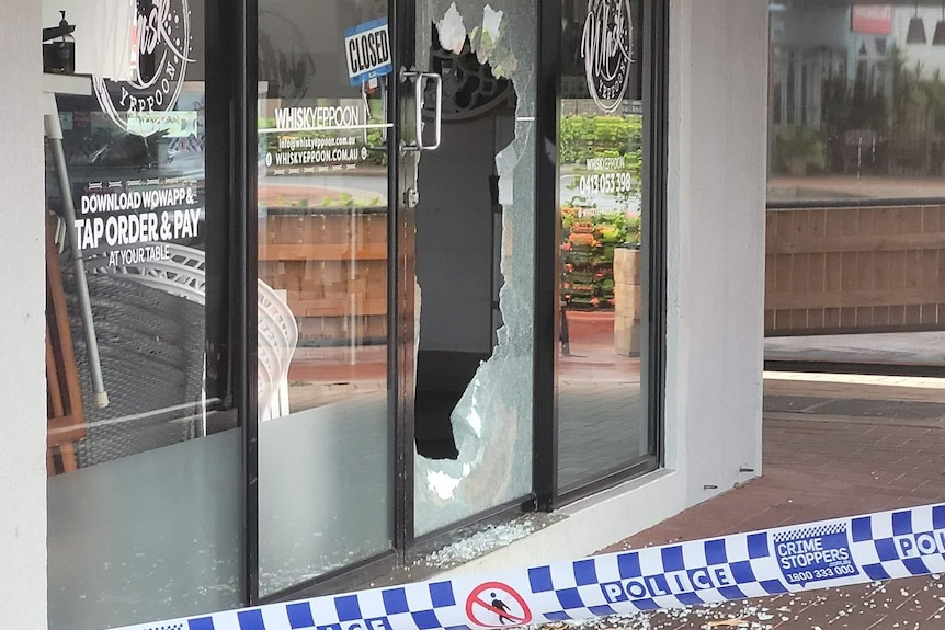 A glass door is shattered in a cafe. Blue and white police tape is visible, and shards of glass are on the floor outside.