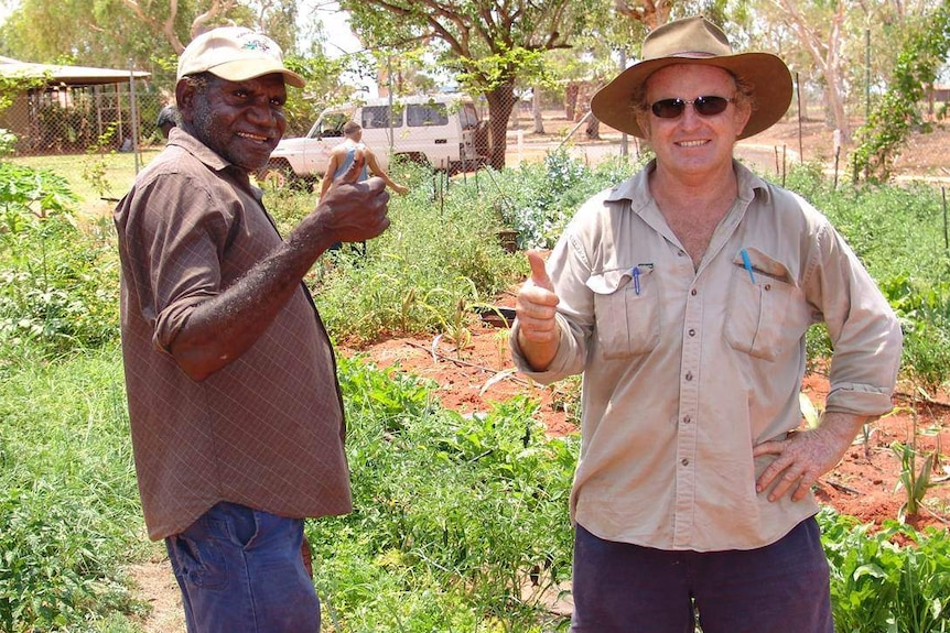 Two men with thumbs up in a garden.