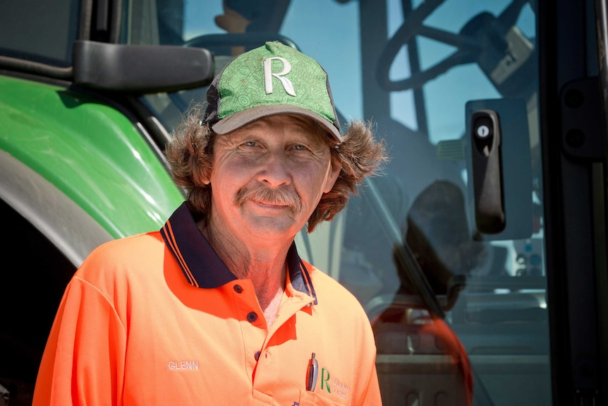 Glenn Bressow stands outside a tractor he drives as part of his job at Rocky Point.