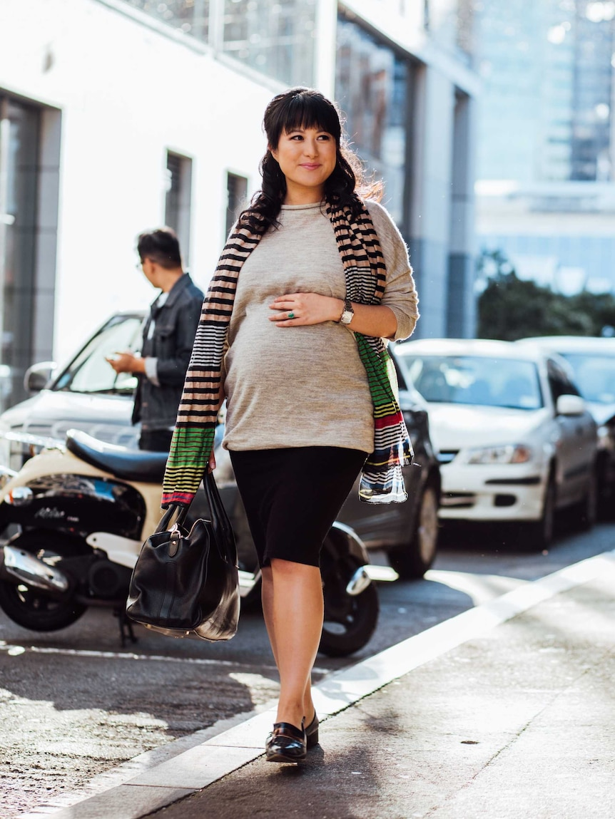 A pregnant woman walking down a street, wearing a scarf and smiling wearing flats as a fashionable alternative to high heels.