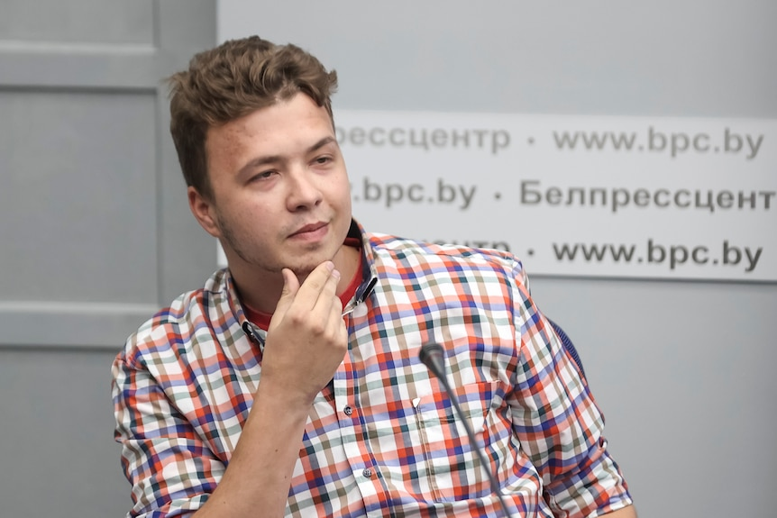 A waist-up photo of Jailed Belarus journalist RomanProtasevichtakes part in a press conference.