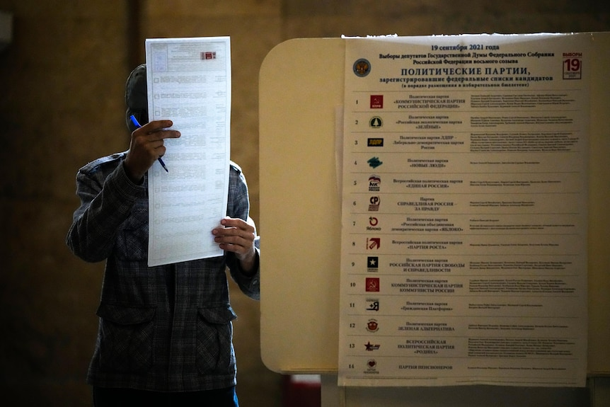 A man reads his ballot at a polling station while holding a blue pen in his right hand.