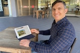 Man sits at table, looking at iPad with a house advertisement on the screen.