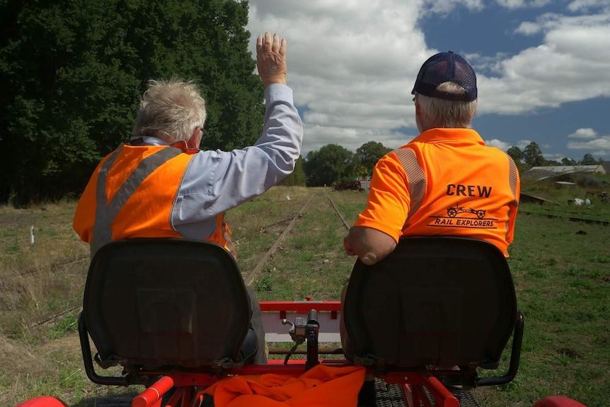 Two men riding a tandem bike along a railway track.