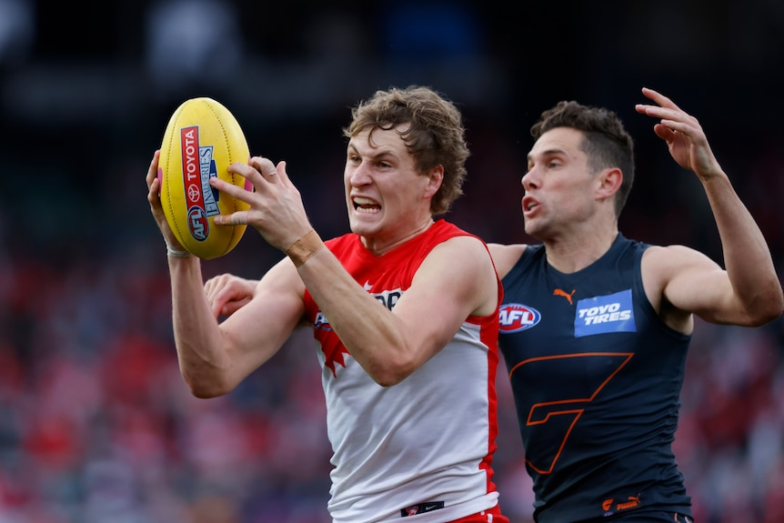 Jordan Dawson catches a yellow AFL ball in front of his face and grimaces