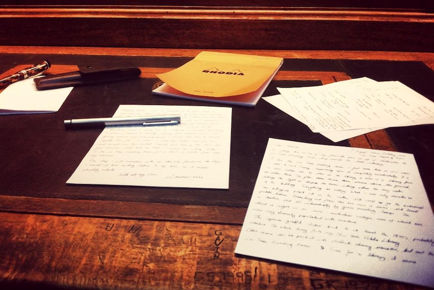 A table scattered with pen and paper.