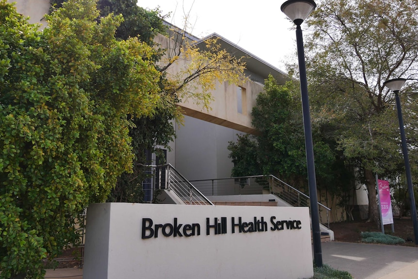 """A photograph of the entrance to a hospital with a sign reading """"Broken Hill Health Service""""."""