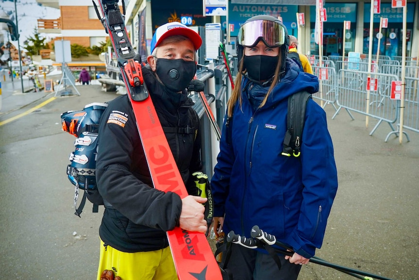 A man and a woman dressed in face masks and ski gear