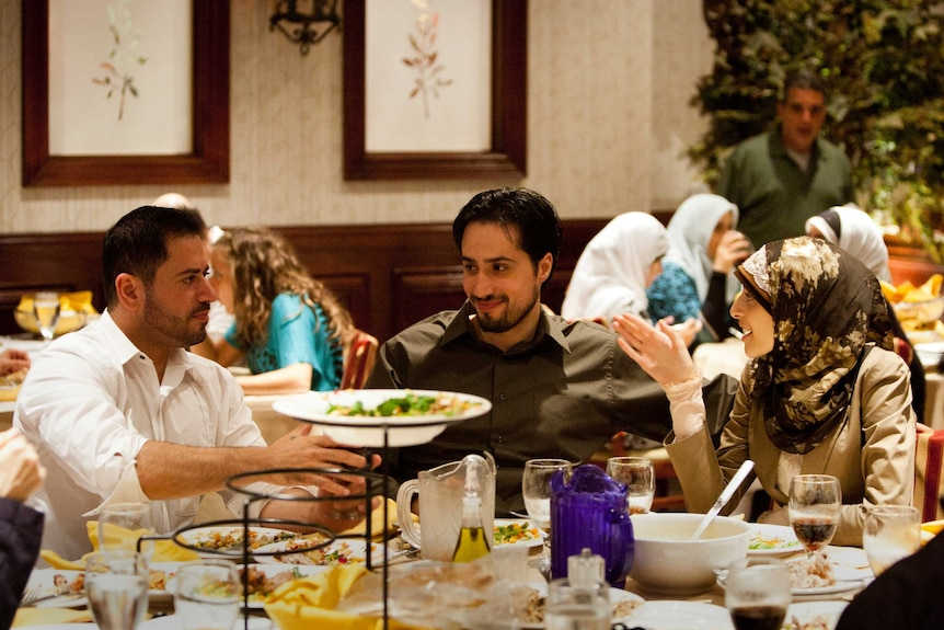 Two men and one woman in hijab eat dinner