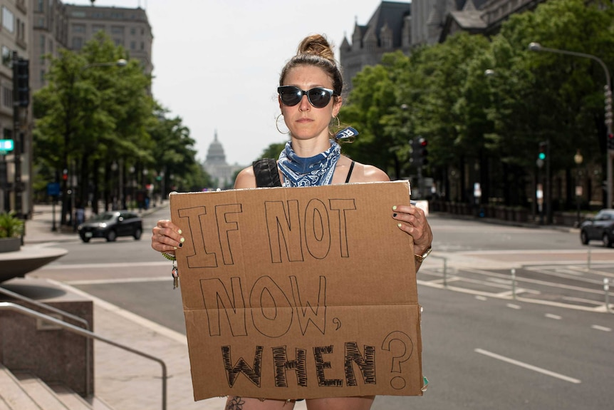 A white woman in DC holding a sign reading 'if not now, when?'