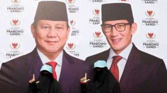 Women pose in front of posters of Indonesian figure Prabowo Subianto.