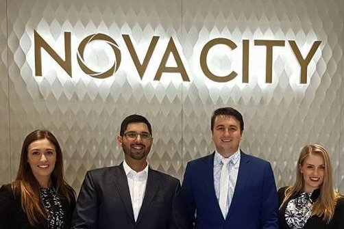 Four professionally dressed people pose in front of a Nova City sign.