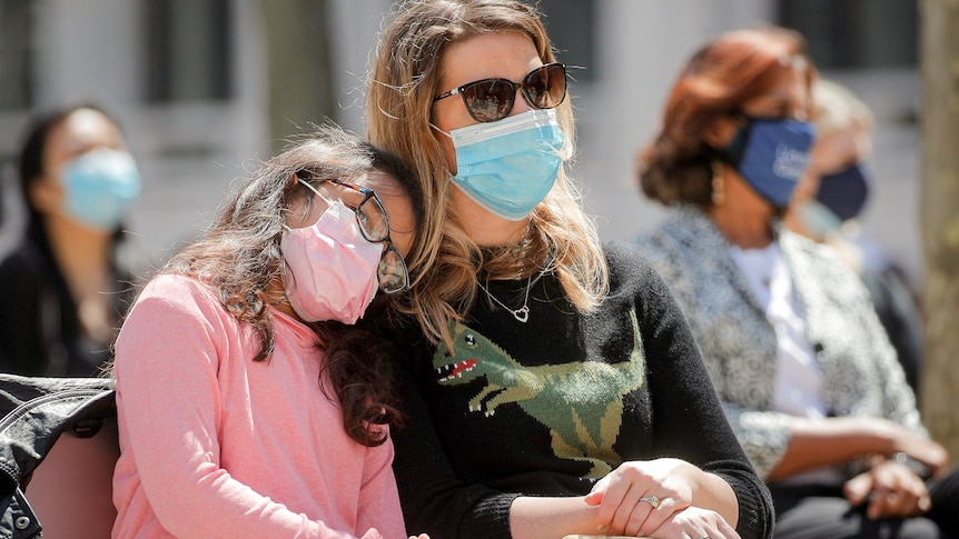 A woman wearing a mask sits starting ahea with her daughter leaning on her.