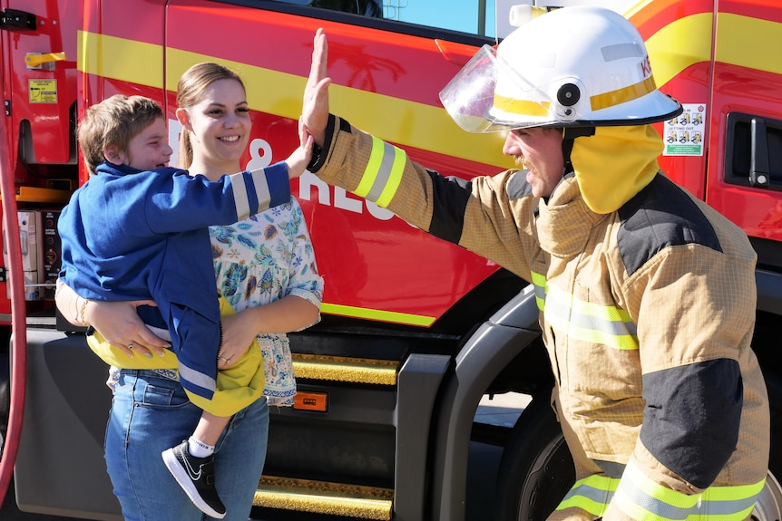 a woman holds a young boy in her arms, standing in front of a fire truck, as the boy high-fives a fire fighter