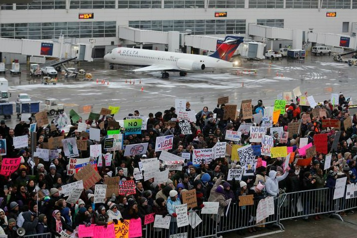 Protesters stand on the tarmac holding signs in Michigan.