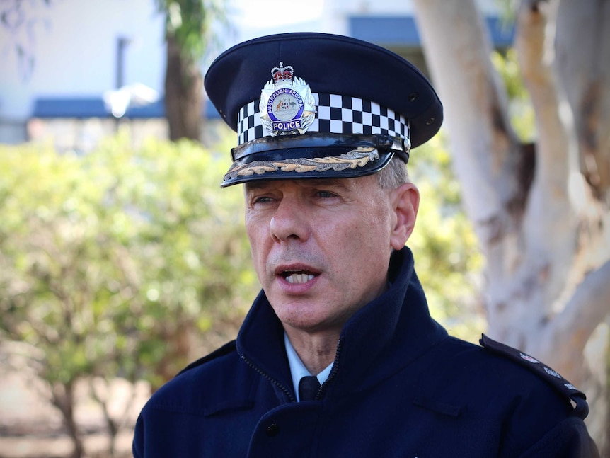 A police officer, in full uniform, including a hat, speaking.
