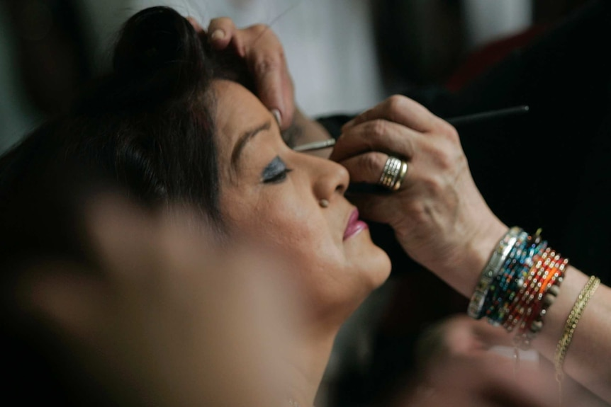 An inmate has her eyeshadow and liner applied prior to the pageant.