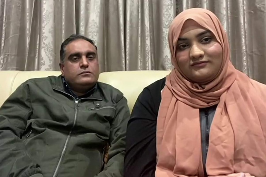 Tourqeer Balouch (left) sitting on a sofa with his daughter Noor Ul Ain (right)