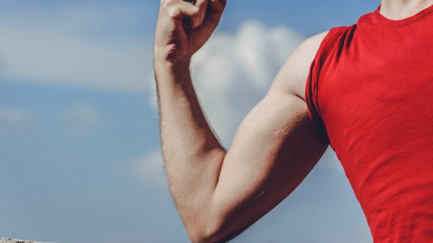 Close-up of man's arm flexing, with the blue sky in the background.