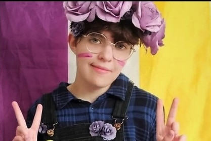 A person wearing a crown of roses sitting in front of a purple, white and yellow flag doing peace signs