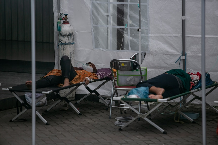 Patients on stretchers receiving oxygen from cylinders in a temporary medical tent.