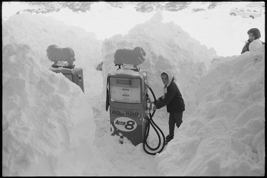 Black and white of old petrol bowser covered by snow and person trying to take the nozzle