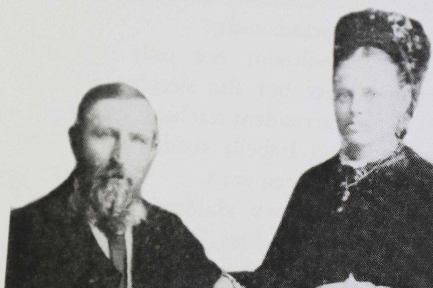Old fashioned photograph of couple from early 1900s posing on chair