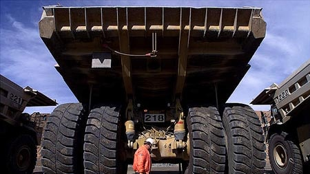 A truck driver walks past a giant mining truck at the largest open pit gold mine in Australia in Kalgoolie.