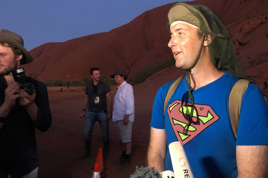 A white man wearing a hat with flaps and a Superman t-shirt is interviewed at the base of Uluru.