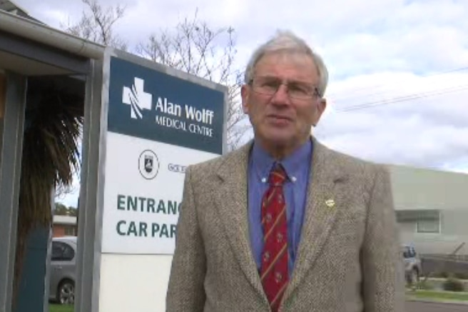 A concerned-looking elderly man stands in front of a doctor's office.