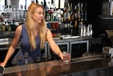 Ms Maddox stands behind the bar, placing a glass on the bar in front of her. Bottles of liquor are behind her.