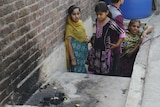 Pakistani residents stand at the site where a teenager was burnt alive by her mother.