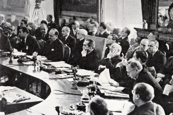 A room full of officials sit in a room watching an address (out of frame). black and white