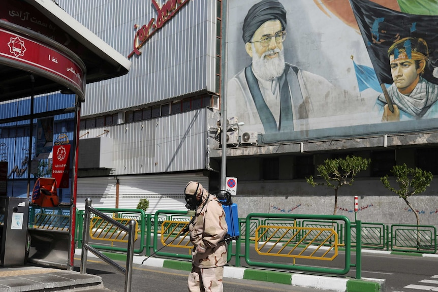 A man in hazmat gear spraying disinfectant near a huge mural  of the Supreme Leader of Iran