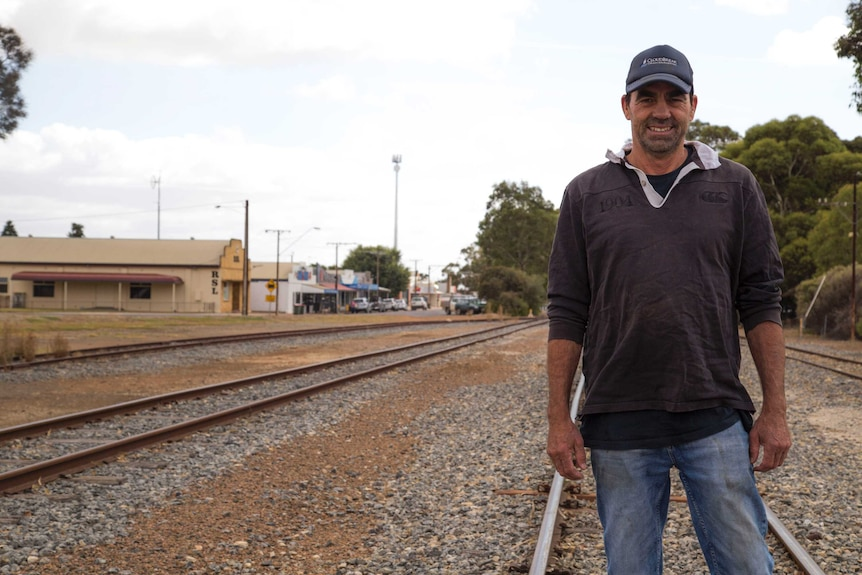 A main in jeans, a jersey top and a baseball cap smiles as he stands on one of several railway lines running parallel.