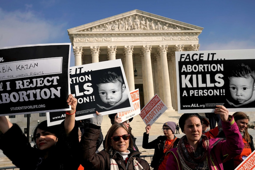 """Protesters standing out the front of the US Supreme Court building holding signs which read """"Face it...Abortion kills a person"""""""