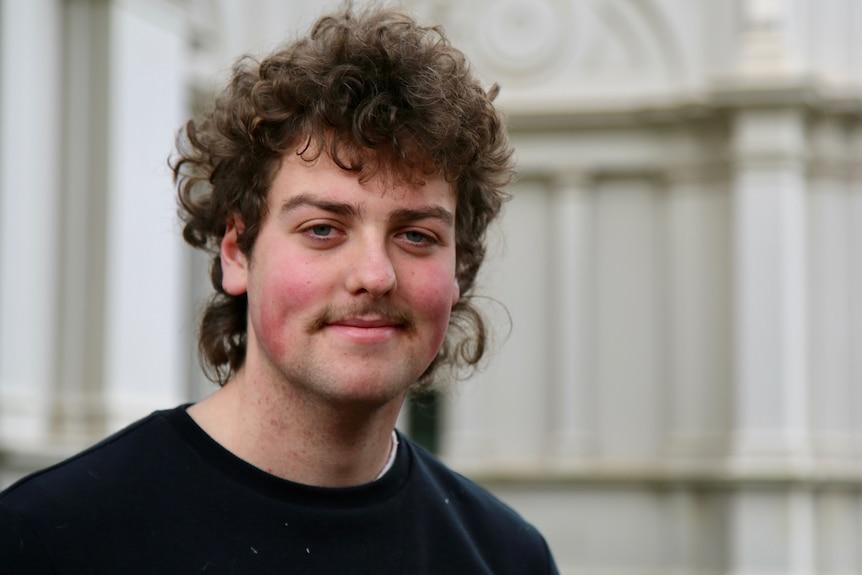 Un bărbat cu părul creț și mustața zâmbind.