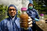Ali Khalid holds a jar with a sewage sample inside.